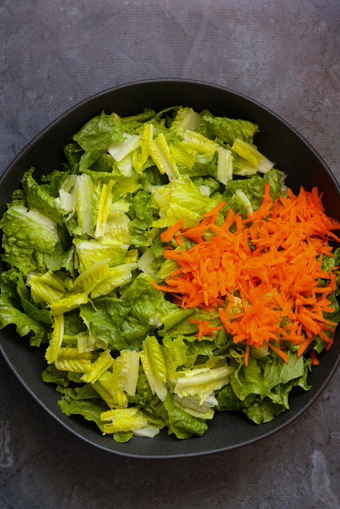 lettuce and carrots in black bowl
