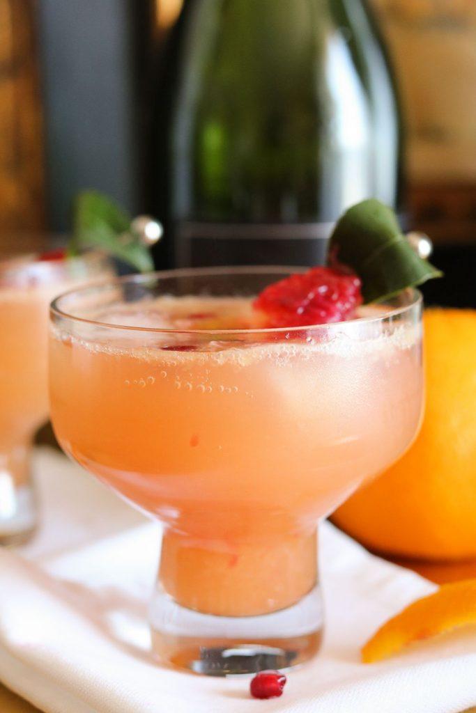 pomegranate blood orange cocktail in glass with garnish