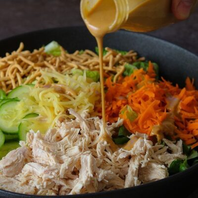 creamy sesame dressing poured onto classic Chinese Chicken Salad