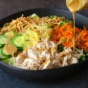chinese chicken salad ingredients in black bowl with salad dressing being poured onto