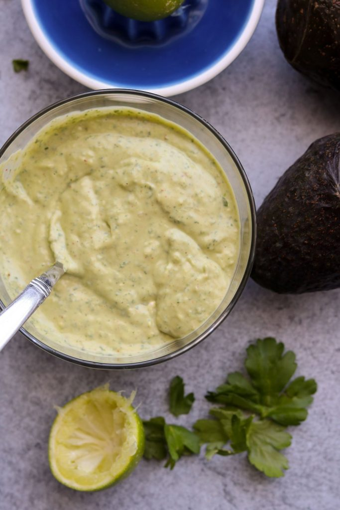 avocado dressing in clear bowl with lime and parsley
