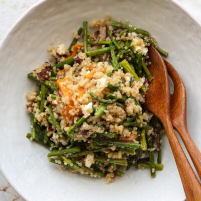 warm quinoa salad in bowl with serving utensils