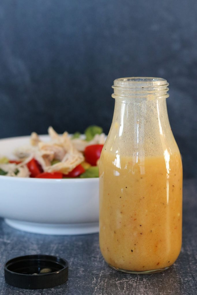 white balsamic honey mustard in bottle with salad in the background