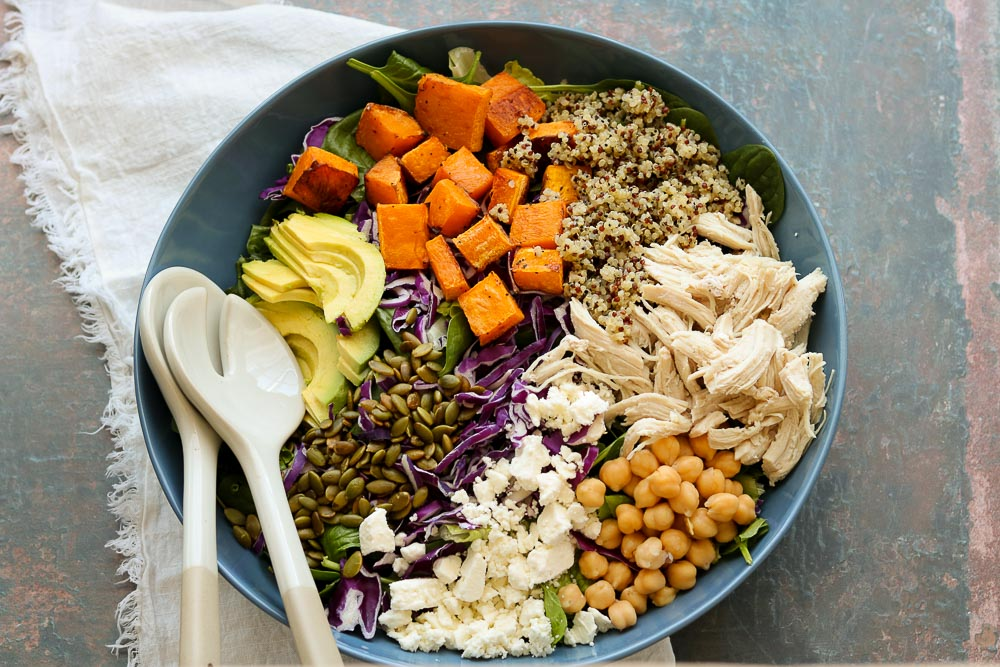 colorful superfood salad in bowl with serving utensils