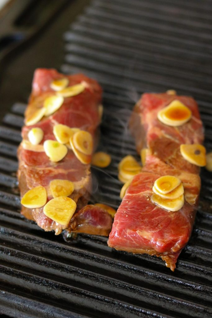raw flat iron steaks on stove top grill