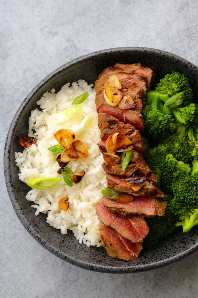 lemon soy flat iron steak with crispy garlic in bowl with rice and broccoli