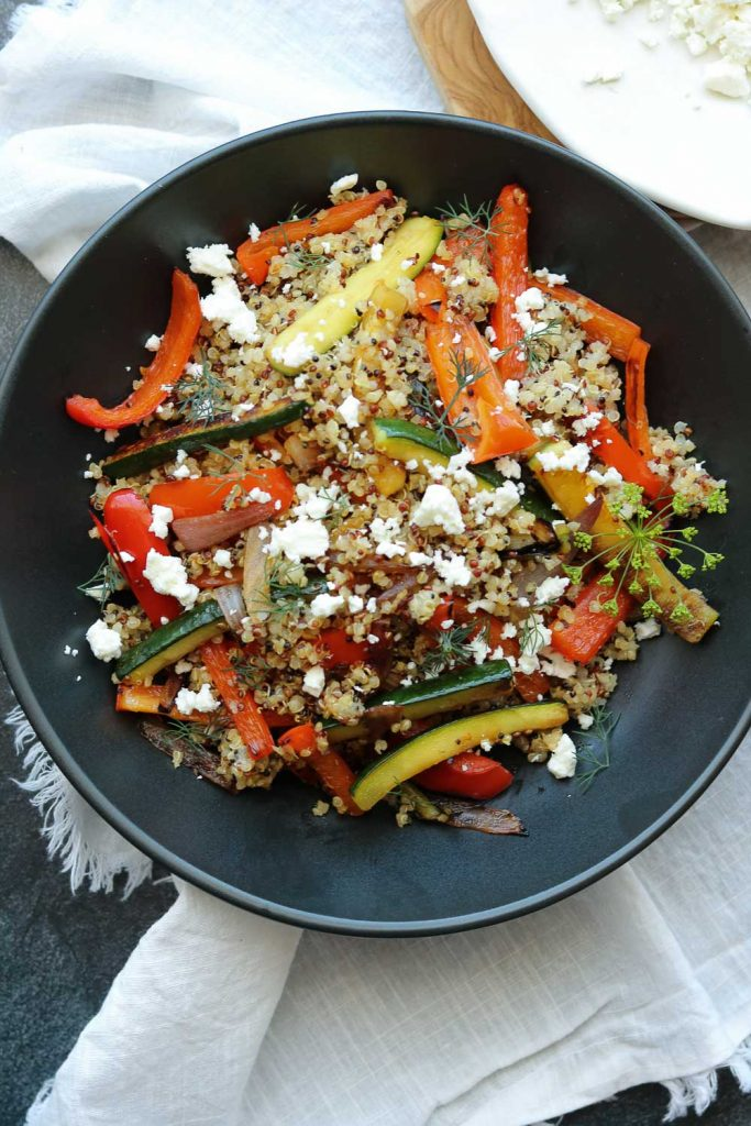 roasted vegetable quinoa with feta in black bowl with napkin