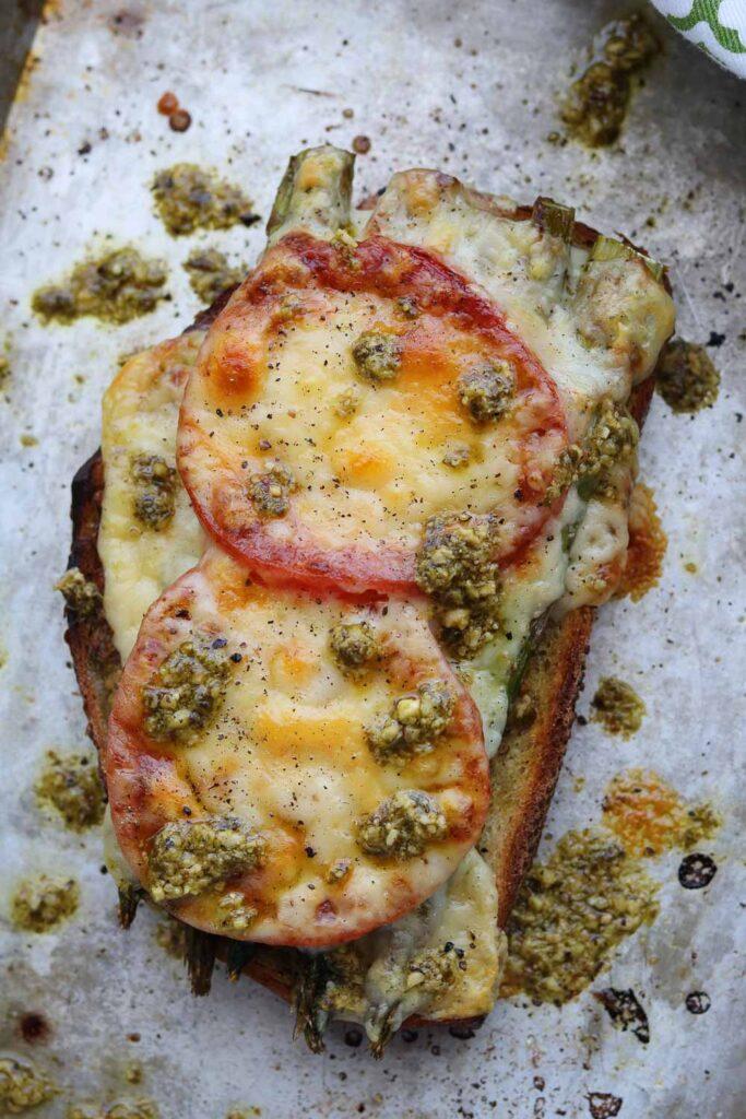 roasted asparagus tomato pesto melt on baking sheet with pesto drizzle