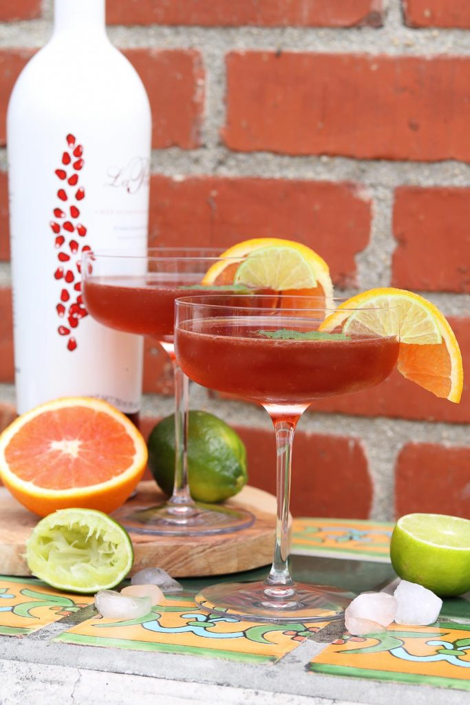 Two Pomerita Cocktails with orange, lime and ice against brick wall