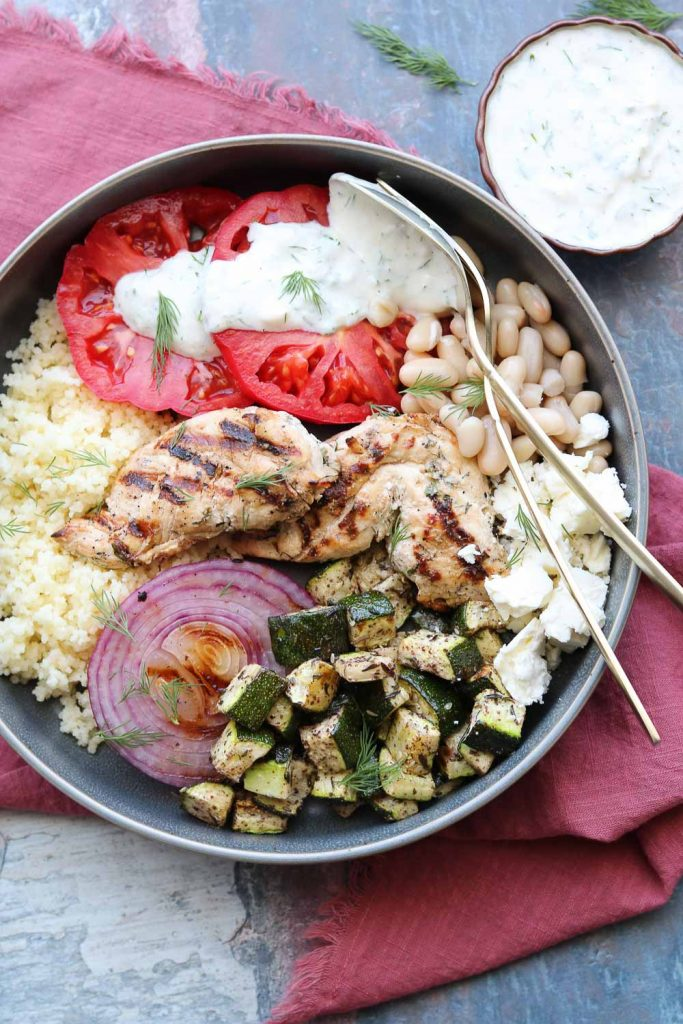bowl with grilled chicken vegetables with yogurt dill dressing on napkin