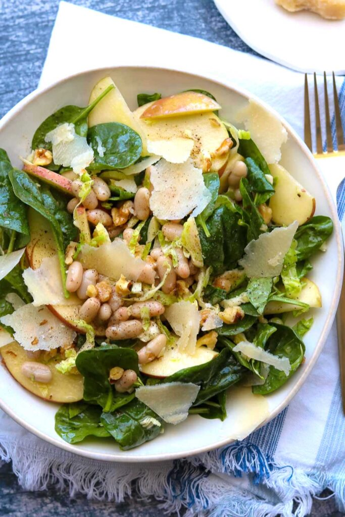 apple spinach white bean salad on plate with napkin and fork