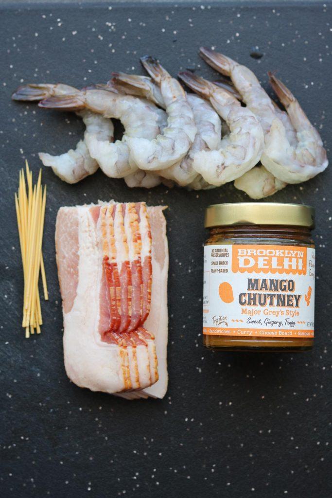 raw shrimp, skewers, bacon and jar of mango chutney
