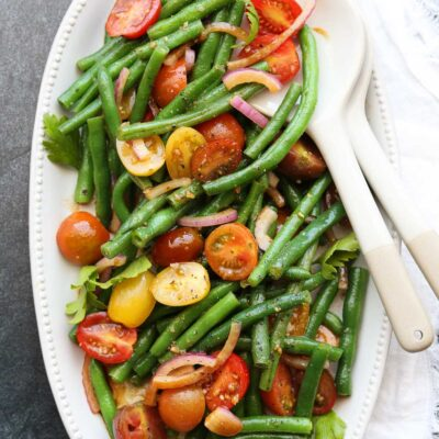 green bean tomato salad on serving platter with utensils