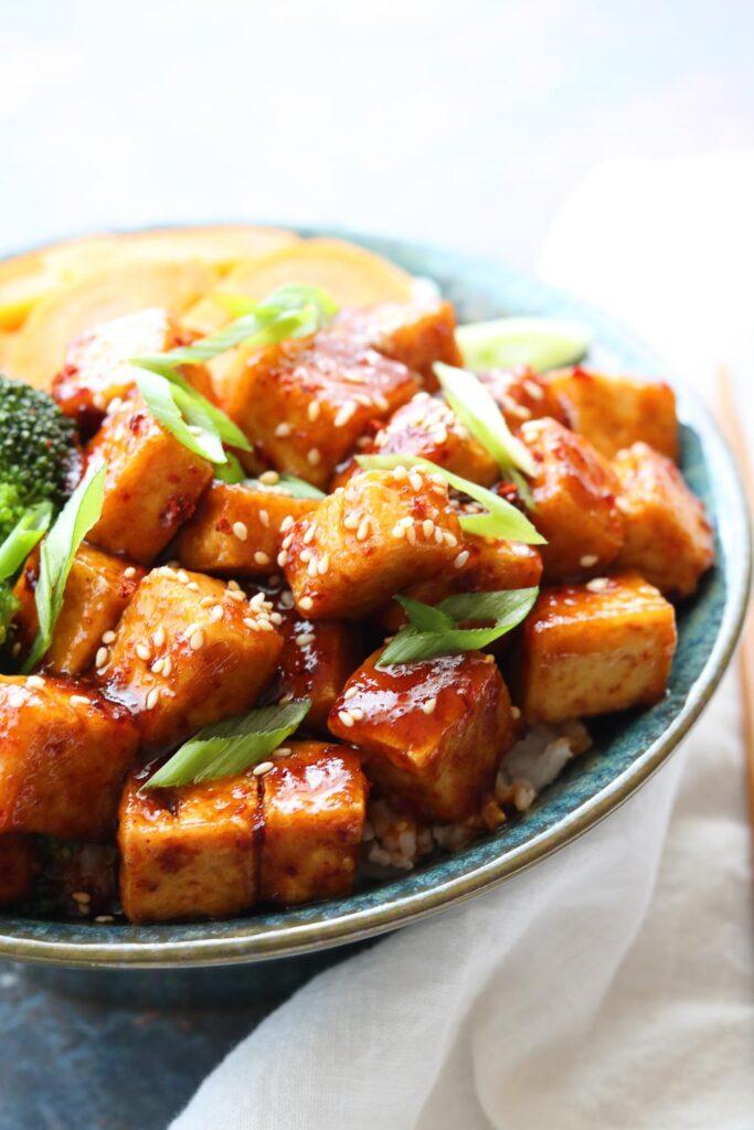 spicy korean style tofu in bowl with veggies and white napkin