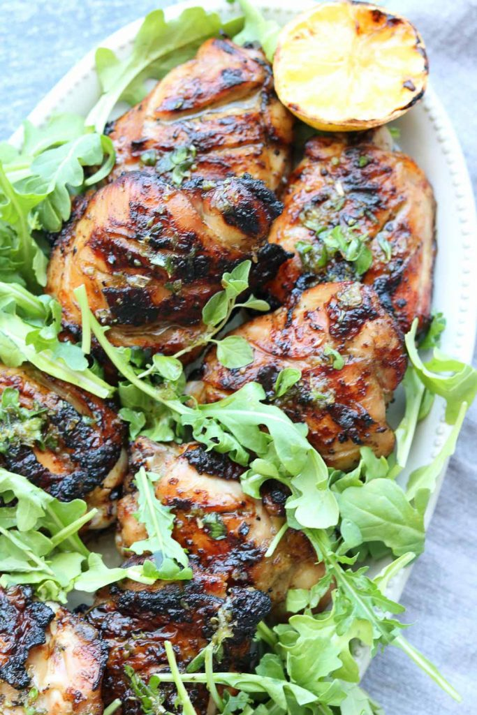 grilled chicken with salmoriglio sauce on platter with arugula