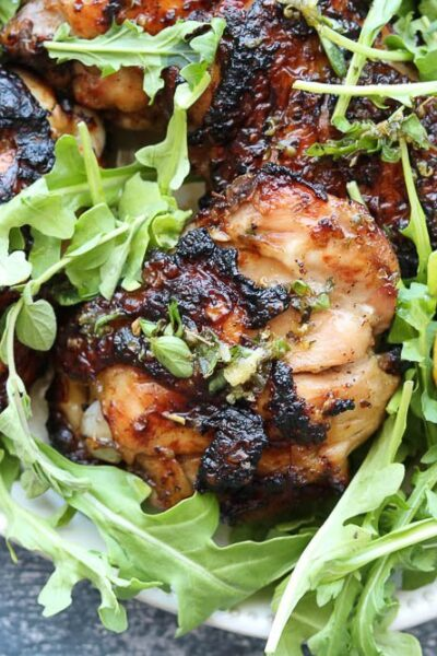 grilled chicken with salmoriglio on platter with arugula and grilled lemon