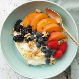 square image of summer fruit bowl with yogurt berries and peaches