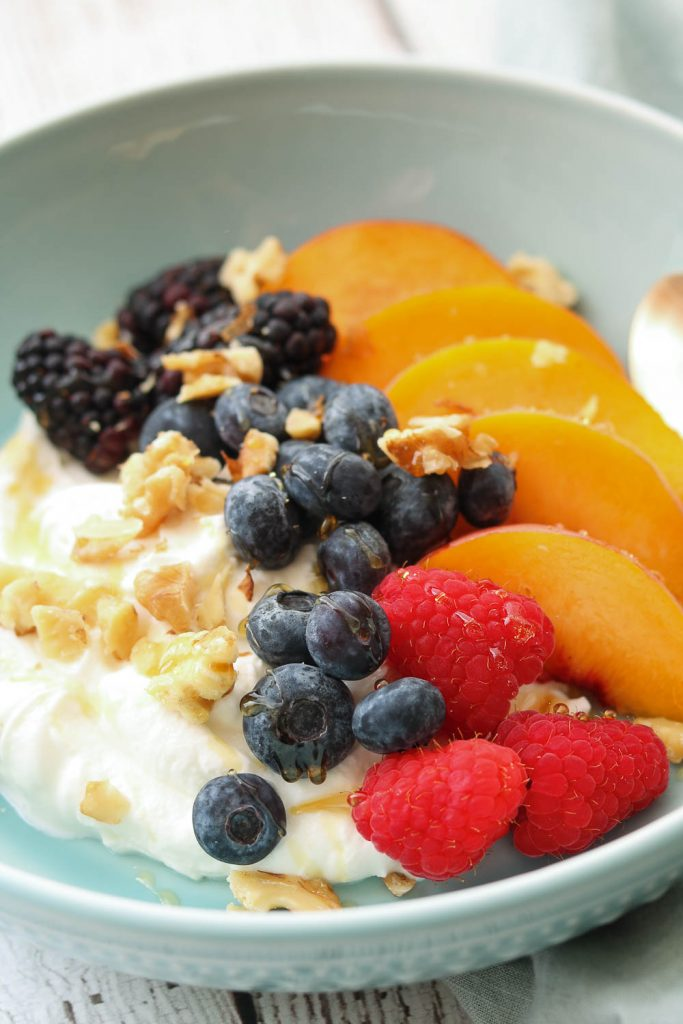 summer fruit yogurt bowl with nuts and spoon