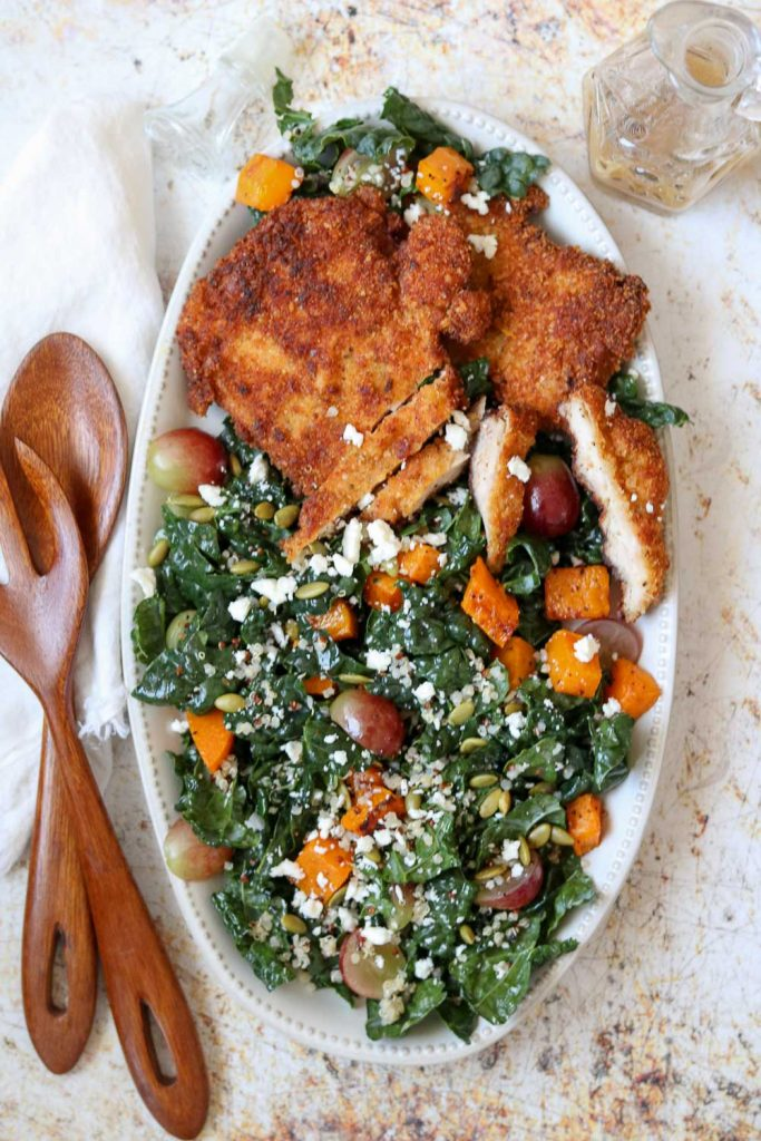 chicken schnitzel and kale autumn salad on platter with serving set