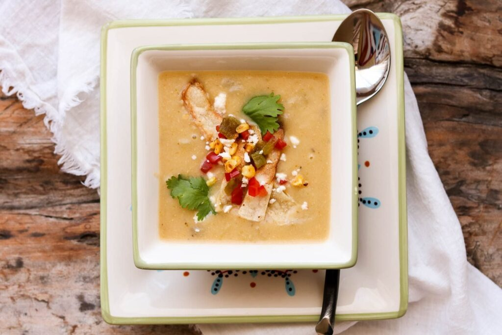 creamy potato hatch chile soup in square bowl with spoon and napkin