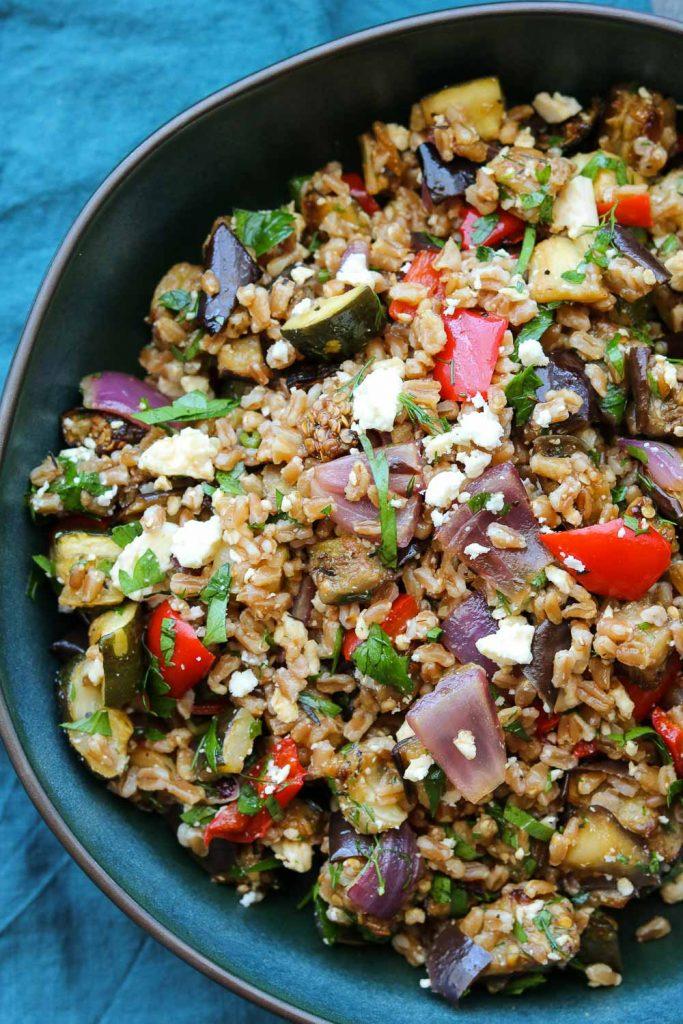 balsamic roasted vegetable grain salad in bowl with dark napkin
