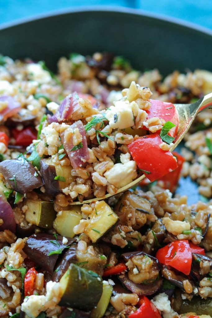 close up of balsamic roasted vegetable salad on serving spoon