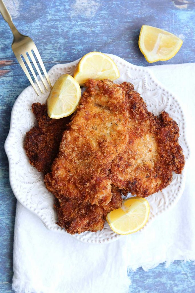easy chicken schnitzel on white plate with lemon garnish white napkin and fork