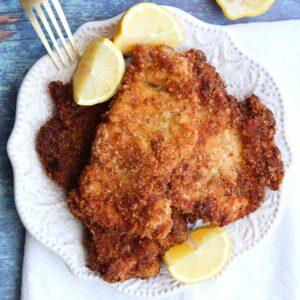 chicken schnitzel square with lemons fork on white plate