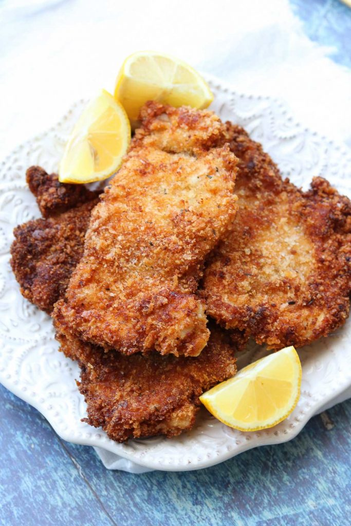 close of easy chicken schnitzel with lemon wedges